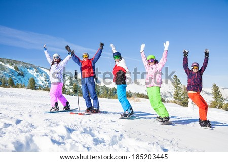 Skier and snowboarders in a row lifting hands up