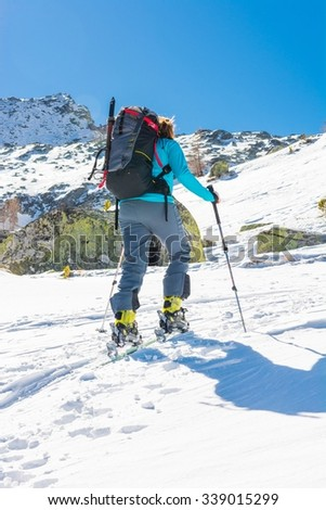 Skier ascending a slope. Ski touring where skier is tackling a steep slope.
