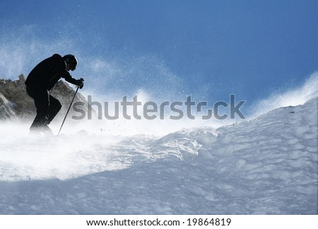 Skier climbs on top of the mountain with strong wind and snow in air