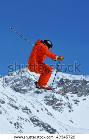 skier dressed in orange performing a high jump with skis together with the alps in the background - stock photo