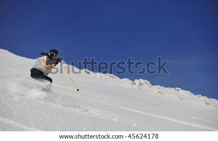 skier free ride downhill at winter season on beautiful sunny day