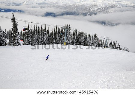 Skier going down the hill and people riding a chairlift at Whistler-Blackcomb ski resort in Canada - stock photo