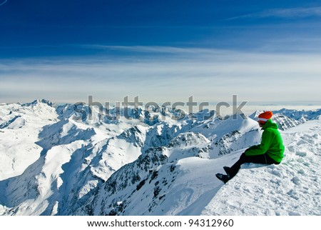Skier having a break, sitting on the edge and being overwhelmed by beauty of high mountains, Austrian Alps below