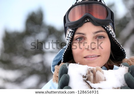 Skier holding snow containing jagged wood - stock photo