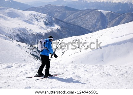 skier in blue skisuit skiing against snowy mountains