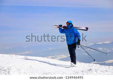 skier in blue skisuit walking against snowy mountains