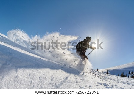 skier in deep powder on a steep slope - stock photo