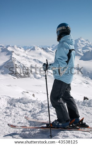 skier in helmet looking to the snowy mountains