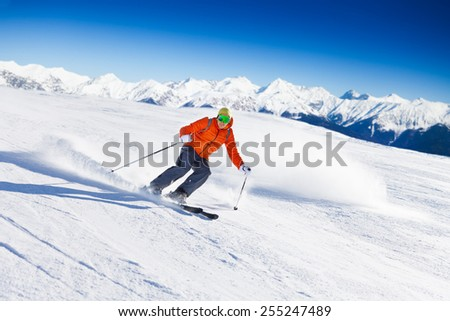 Skier in mask slides fast while skiing from slope - stock photo