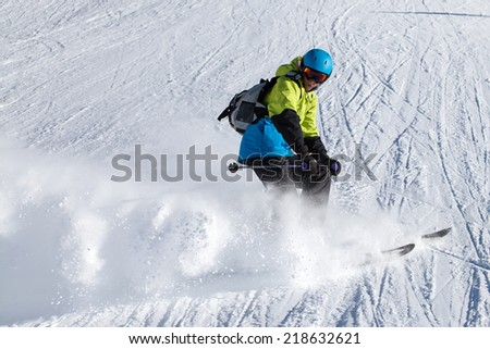 Skier in mountains does turn, prepared piste