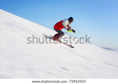 Skier in red jacket riding on hill. Motion blurred snow and clear blue sky