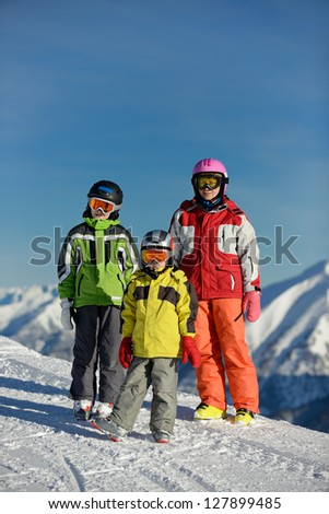 skier in the beautiful alps. Kids and adults in the high snowy cloudy mountains in winter.