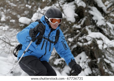 Skier is free riding between trees - stock photo