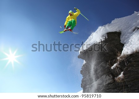 Skier jumping against blue sky - stock photo