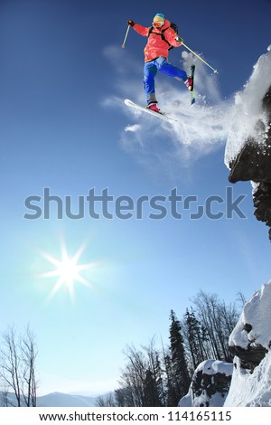 Skier jumping against blue sky from the  rock - stock photo