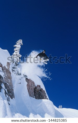 Skier jumping from mountain ledge against deep blue sky - stock photo