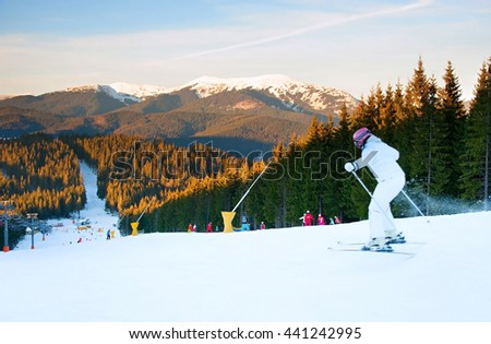 Skier jumping on a mountains slope at sunset - stock photo