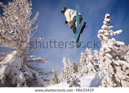 Skier jumping over blue sky - stock photo