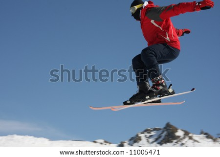 Skier jumps into the air with mountains behind - stock photo