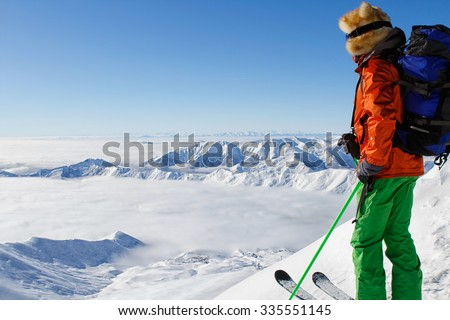 Skier looking at ski resort and clouds below him - stock photo