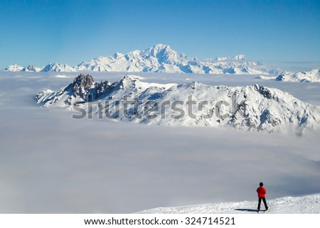 Skier looking at the Mont Blanc over a sea of clouds, the Alps, France