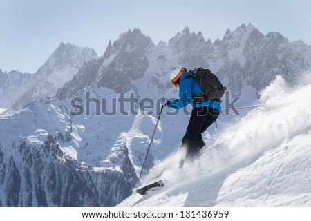 Skier making turn in powder snow with mountains in background.