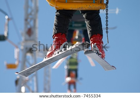 skier moving up on the chair lift - stock photo