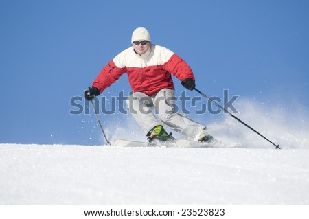 Skier on a slope against blue sky - stock photo
