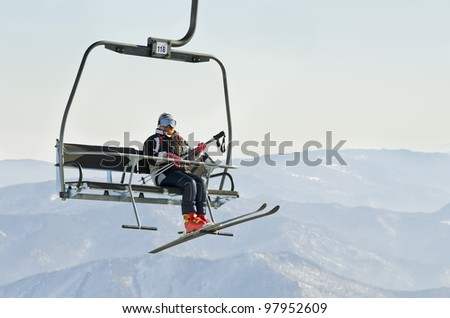 Skier on ski lift at resort in Siberia - stock photo