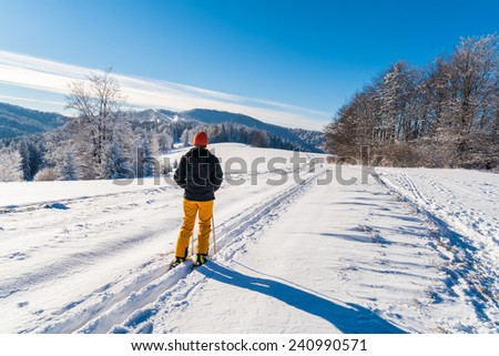 Skier on track in winter landscape of Beskid Sadecki Mountains on sunny day, Poland