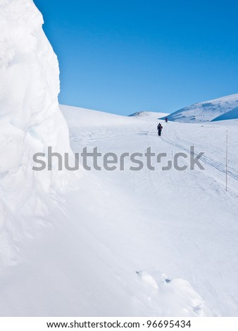 Skier passing a snow formation in norwegian mountain at easter - stock photo
