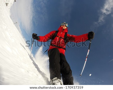 Skier performs a high speed turn on a ski slope. From the ski tip point of view. Sunny winter day. Concepts: vacation, speed, fun. - stock photo