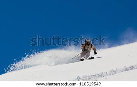 Skier rides up a steep slope in the soft snow on a sunny day - stock photo