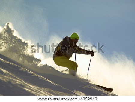 skier rush at full speed in the clouds of snow powder - stock photo
