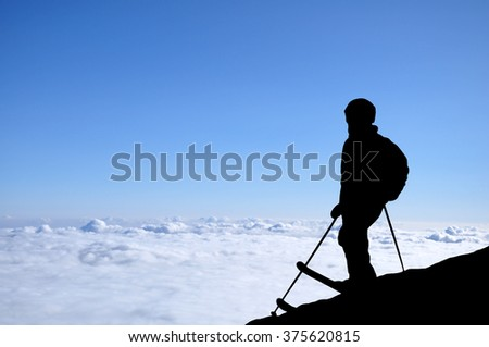 Skier silhouette high in mountains. Skier standing on a hill high above the clouds during a sunset, beautiful colorful sky with clouds in front of him.