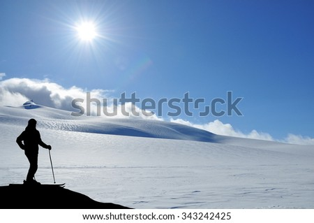 Skier silhouette high in mountains. Skier standing on a slope, snowy hills and sun in front of him. - stock photo