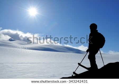 Skier silhouette high in mountains. Skier standing on a slope, snowy hills and sun in front of him.