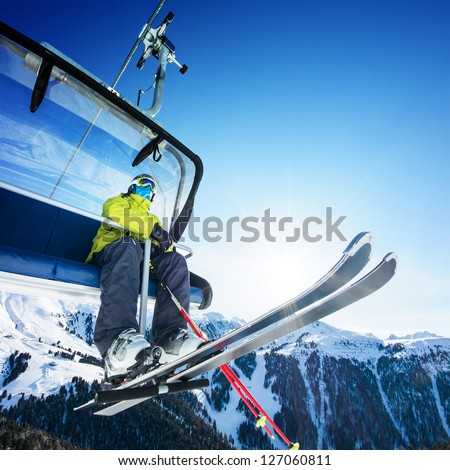 Skier sitting at ski lift in high mountains - stock photo