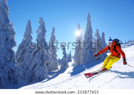 Skier skiing downhill in high mountains against sunshine - stock photo