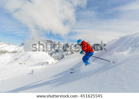 Skier skiing downhill in high mountains, San Martino di Castrozza in Italy - stock photo