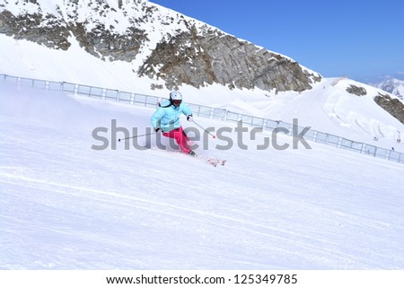 skier skiing downhill on fresh powder snow with sun