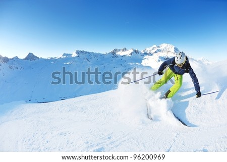 skier skiing downhill on fresh powder snow  with sun and mountains in background - stock photo