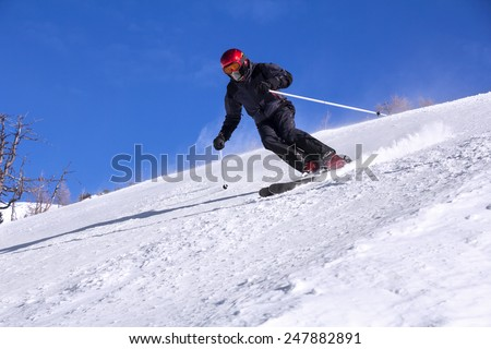 Skier with a mask on face skiing downhill in high mountains and sunny day - stock photo