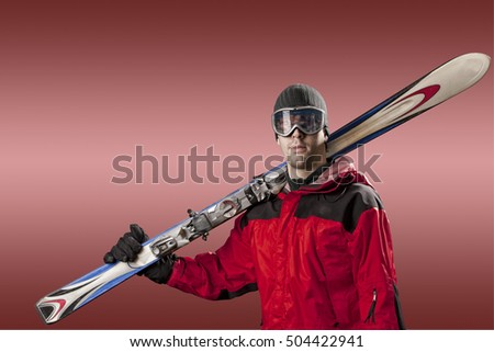 Skier with a red jacket, holding a pair of skis on a red background.