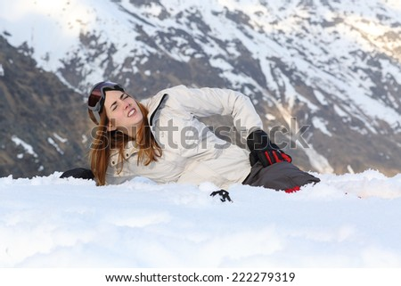 Skier woman hurt lying in the snow of a high mountain - stock photo