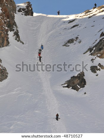 skiers and snowboarders climb a couloir  on a high mountain - stock photo