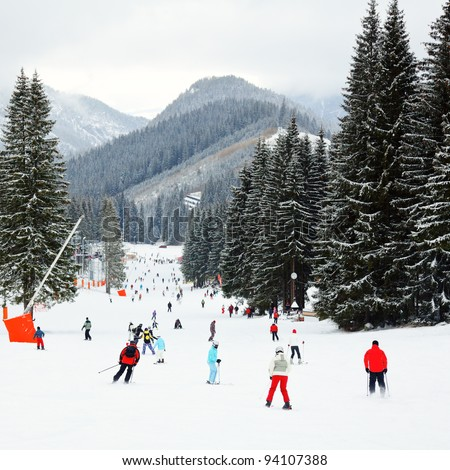 Skiers and snowboarders going down the slope at Jasna ski resort in Slovakia - stock photo