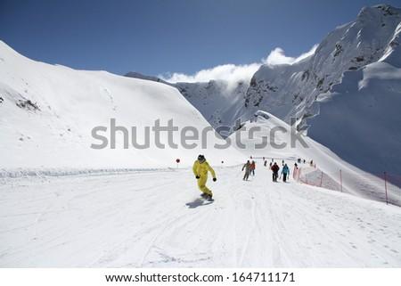 Skiers and snowboarders going down the slope at ski resort. Krasnaya Polyana, Sochi, Russia - stock photo