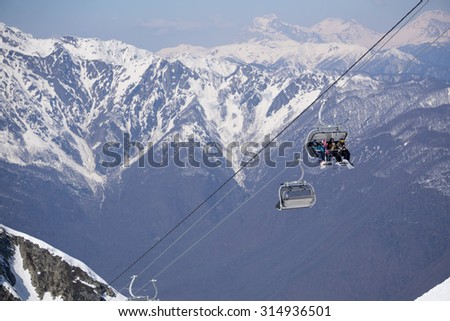 Skiers and snowboarders on a mountain ski lift - stock photo