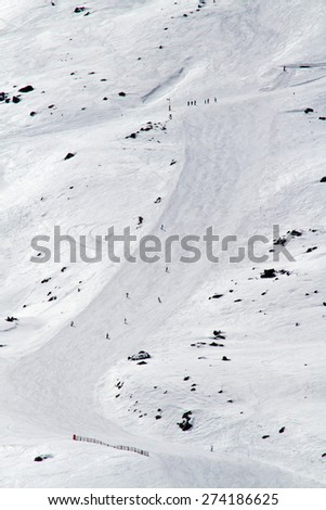 Skiers and snowboarders race down a slope at a winter ski resort in the French Alps. - stock photo